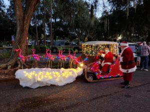 Santa on golf cart sled pulled by 9 flying pink flamingos with antlers, one with a glowing red nose, at the Lakes at Leesburg annual golf cart parade
