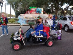 a couple wearing masks in a golf cart decorated with Christmas presents